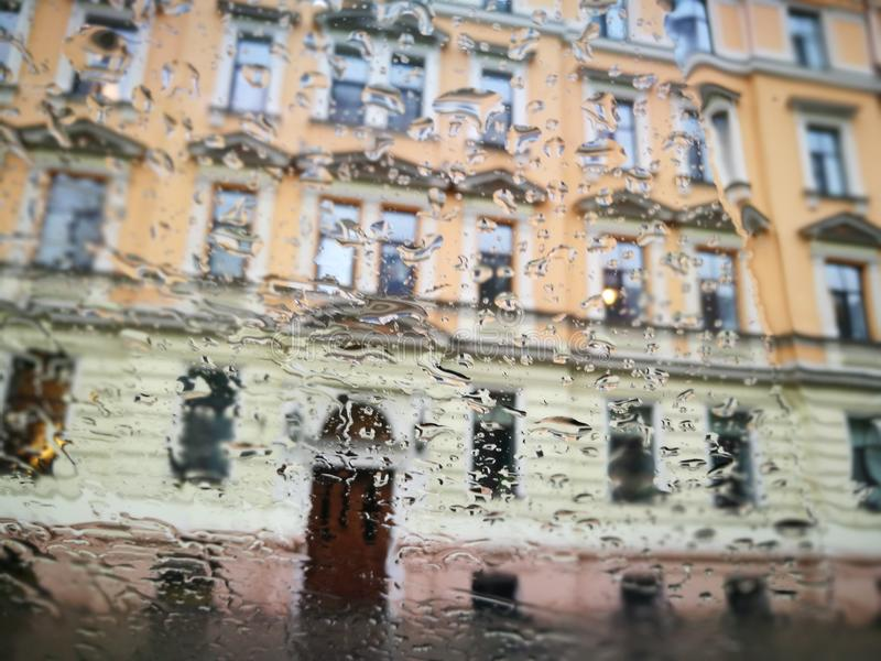 Rainy day in Riga city view to yellow building sparkling Window. Riga Town rainy day Summer time view on street royalty free stock image