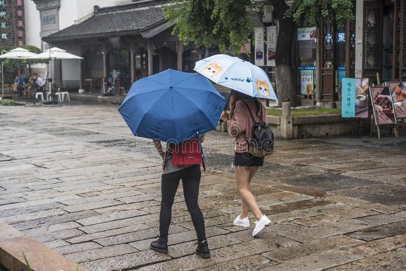 On a rainy day, two young girls with umbrellas walked in the old scenic area of Laomen royalty free stock photos