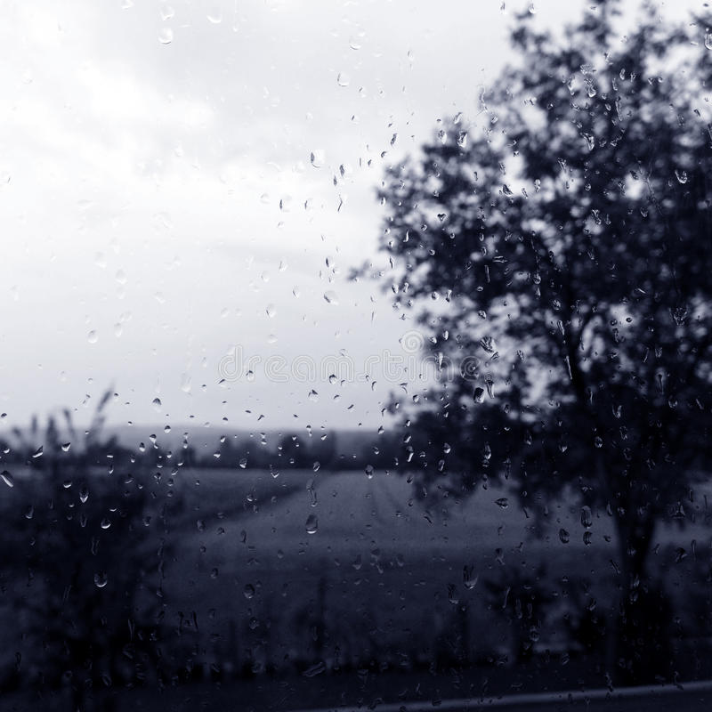 Rainy day window with field countryside view stock photo