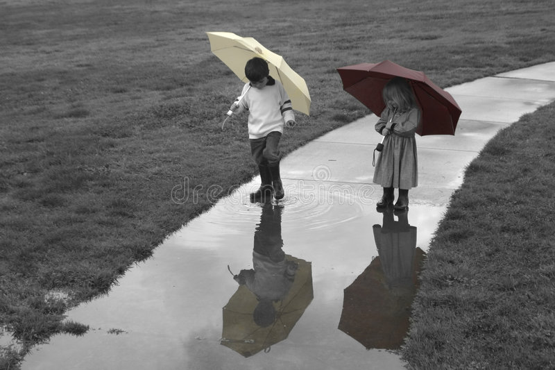 Rainy Days. Kids enjoy a rainy day by passing through a puddle
