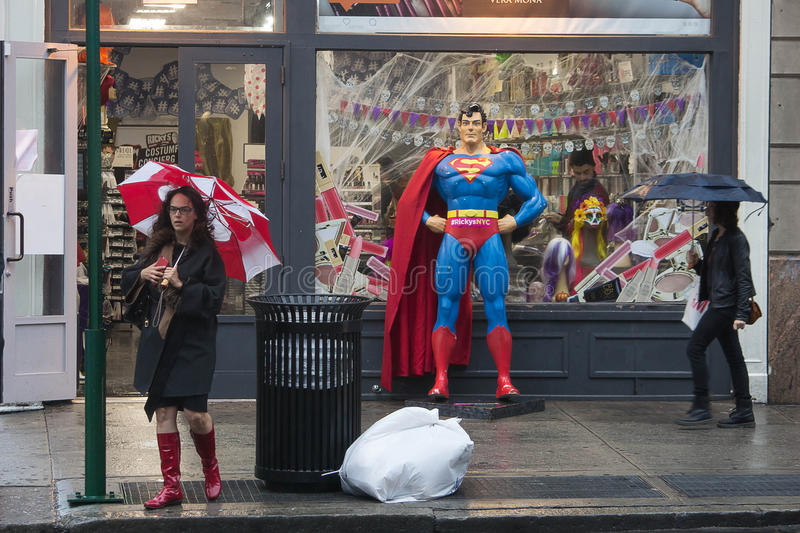 Rainy Days. Lois Lane contemplates crossing the street in front of a statue of Superman along Broadway on a rainy day in October in lower Manhattan stock photo