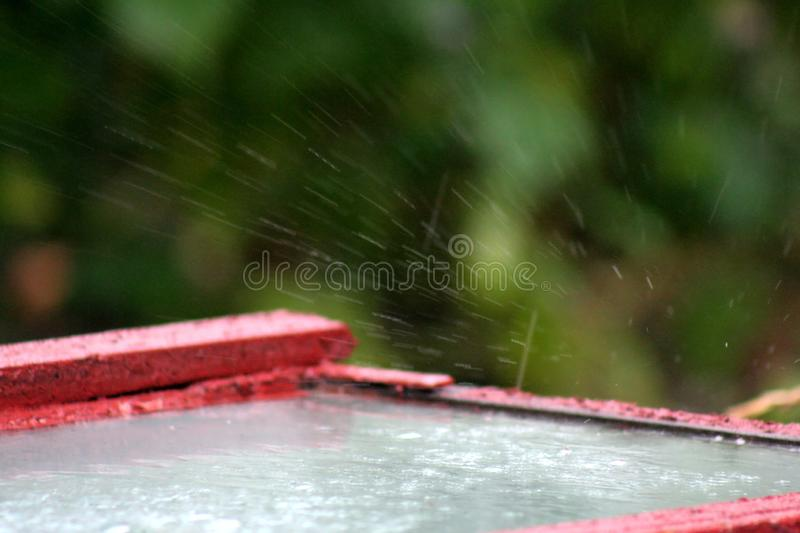 Rainy drops on the old glass. Rainy drops that hit the glass are broken, creating the effect of breaking glass. This phenomenon is often observed during the stock image