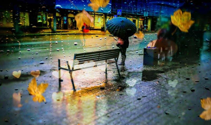 City Rain drops on window evening autumn leaves women  under umbrella  on street urban city blurred light royalty free stock photography