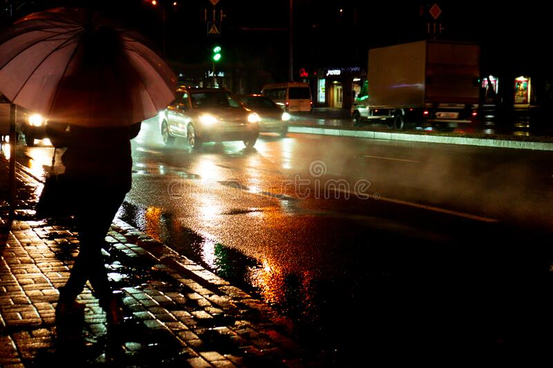 A woman silhouette with umbrella and running traffic with drops of rain. Autumn time. Rainy evening. A woman silhouette with umbrella and running traffic with stock images