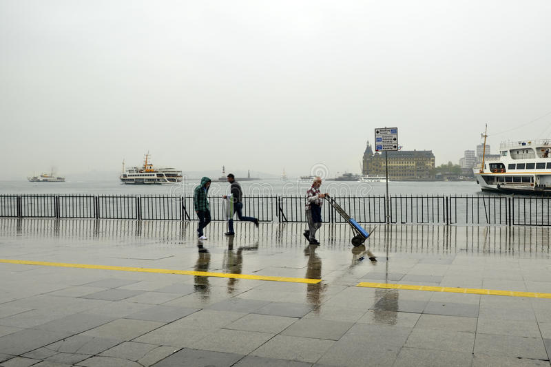 Rainy Istanbul coast, people and ships royalty free stock photography