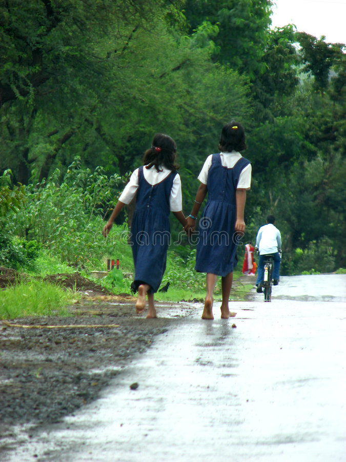 The Rainy Road. Two Indian girls from a village walking on a wet road in rains. Children walk barefeet for miles just to reach their schools, but determined royalty free stock photo
