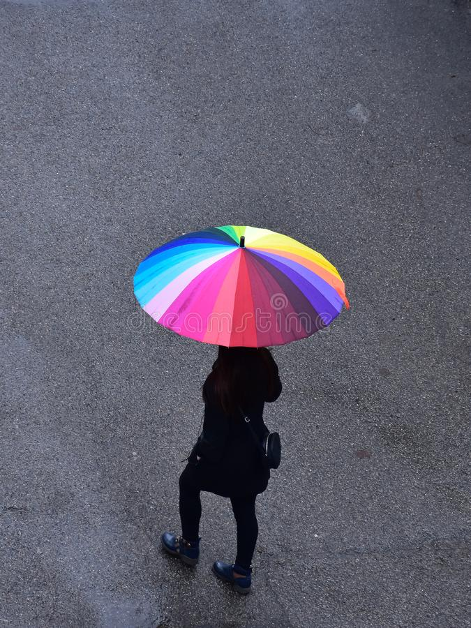 Rainy weather in Almaty, Kazakhstan. A beautiful girl with a cheerful umbrella is walking stock images