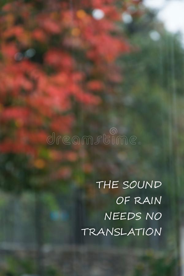 Rainy weather background with text `The sound of rain needs no translation`. Rainy weather background with text - `The sound of rain needs no translation stock photo