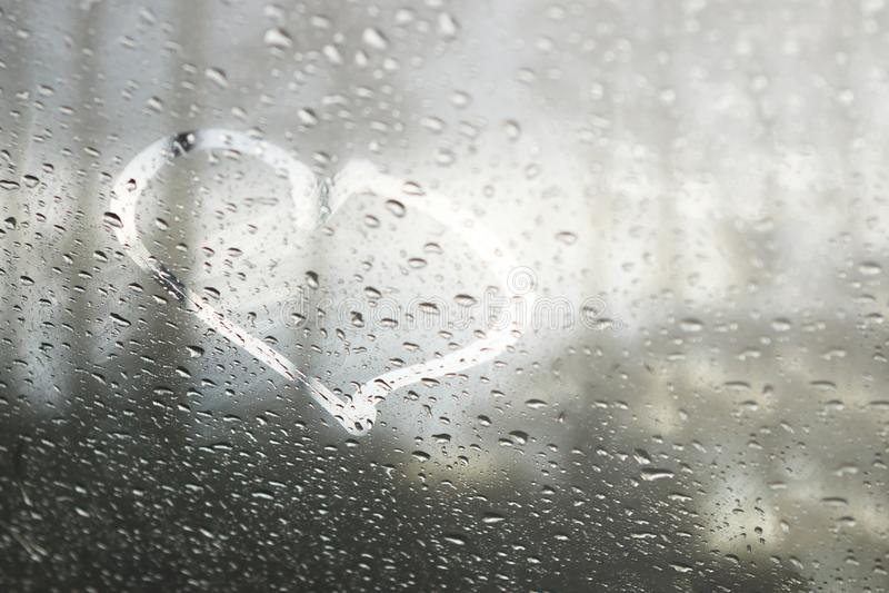 Rainy weather, the inscription heart on the sweaty glass. stock photo
