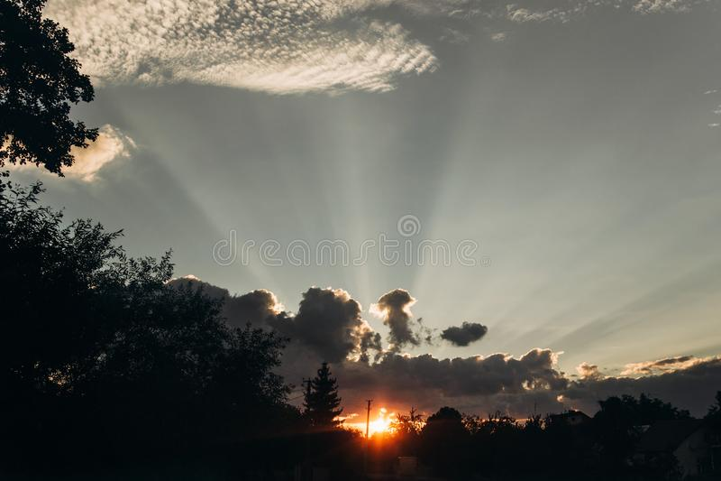 Raios claros surpreendentes dramáticos do sol e do por do sol através das nuvens no céu foto de stock