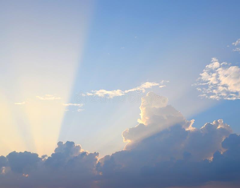 Raios crepusculares amarelos dourados de Sun das nuvens escuras no céu azul - fundo natural Skyscape fotos de stock royalty free