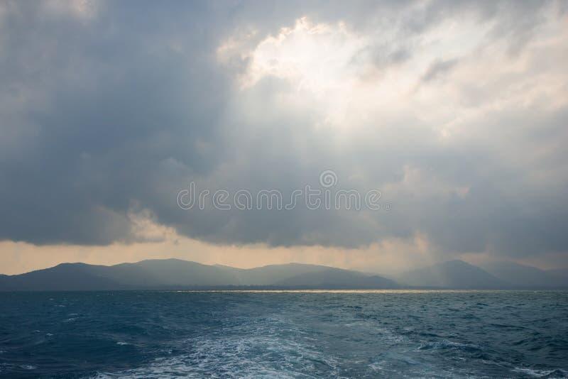 Raios de sol através do furo nas nuvens acima do oceano foto de stock