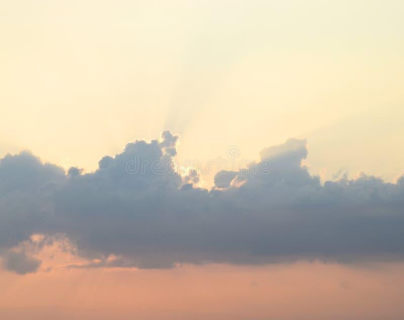 Raios de sol brilhantes de Sun atrás das nuvens escuras em nivelar o céu com cores mornas - fundo natural imagem de stock