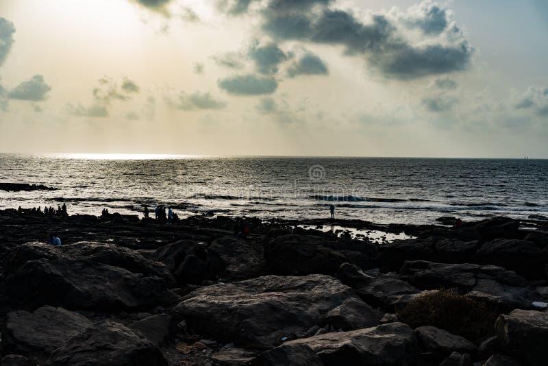 Raios de sol das nuvens e de uma praia rochosa imagens de stock