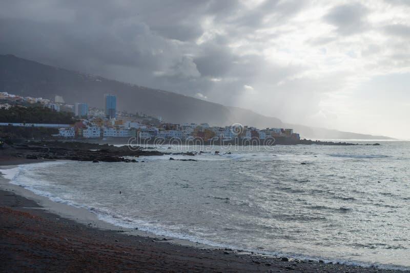 Raios de sol sobre a vila durante o por do sol na praia preta em Pue fotos de stock royalty free