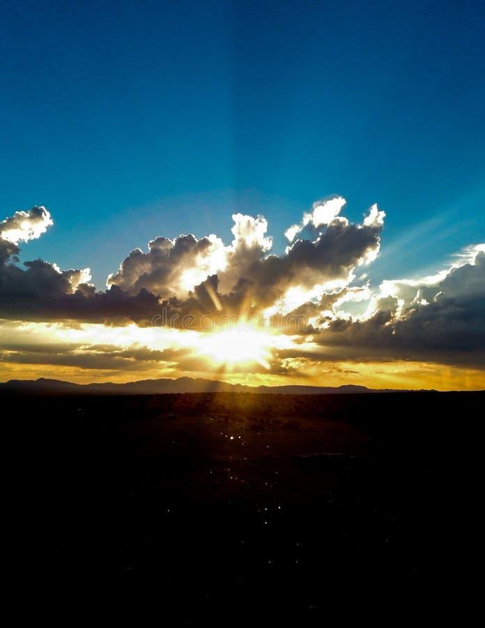 Raios de Sun que espreitam atrás das nuvens escuras e dos céus azuis fotografia de stock