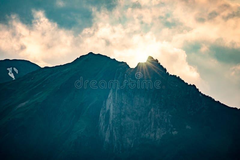 Raios do sol de ajuste sobre uma montanha verde alta com rochas e da neve na parte superior imagens de stock royalty free