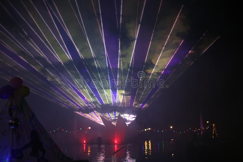 Raios laser durante uma mostra p?blica em diversas cores na ?gua do Ringvaart no antro aan IJssel de Nieuwerkerk fotografia de stock
