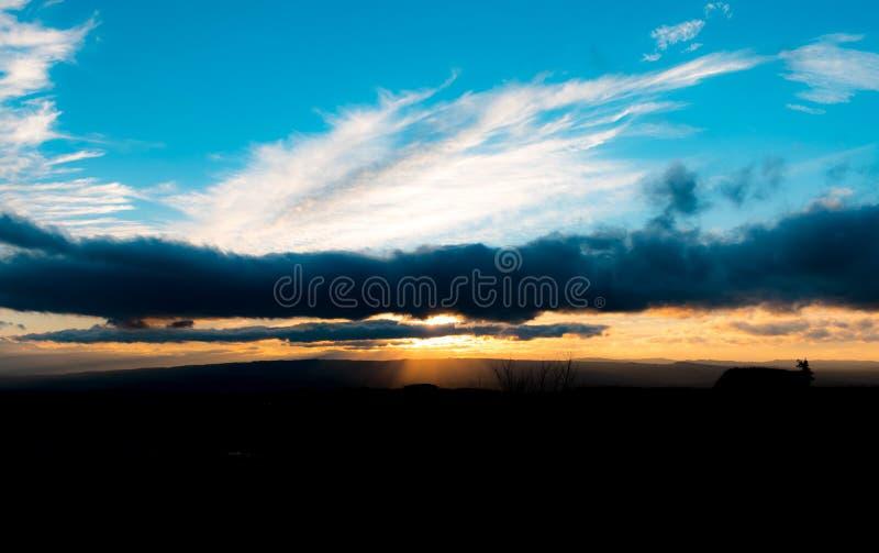 raios solares entre nuvens durante o pôr do sol foto de stock