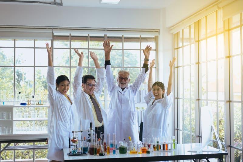 Rais de las manos de los científicos para arriba junto, grupo de trabajo en equipo de la gente de la diversidad en laboratorio, e imagen de archivo