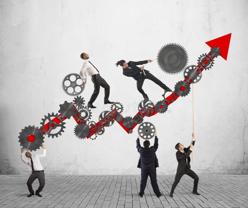 Raise the statistics. Teamwork build an arrow upwards with gears mechanism stock photography