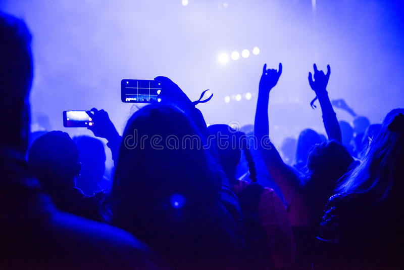 Raised arms holding smart phones to recording a live concert stock photography