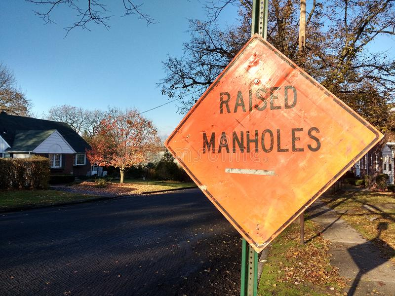 Raised Manholes Sign, Road Work in Residential Neighborhood royalty free stock photography