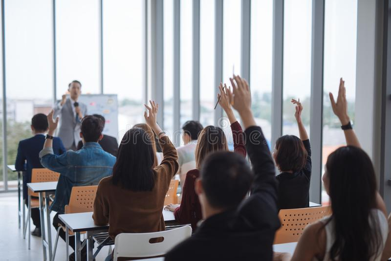 Raised up hands and arms of large group in seminar class room to agree with speaker at conference seminar meeting room. Raised up hands and arms of large group stock image