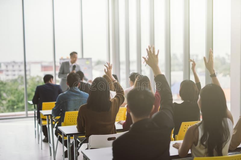 Raised up hands and arms of large group in seminar class room to agree with speaker at conference seminar meeting room. Raised up hands and arms of large group royalty free stock image