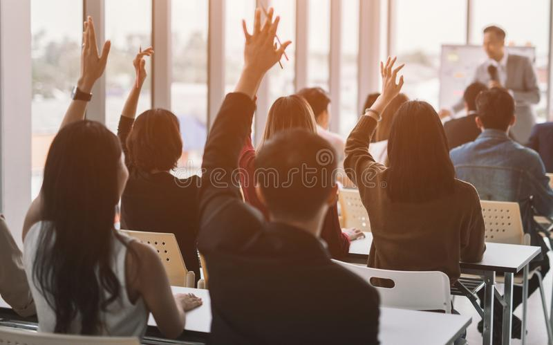 Raised up hands and arms of large group in seminar class room to agree with speaker at conference seminar meeting room. Raised up hands and arms of large group royalty free stock photo