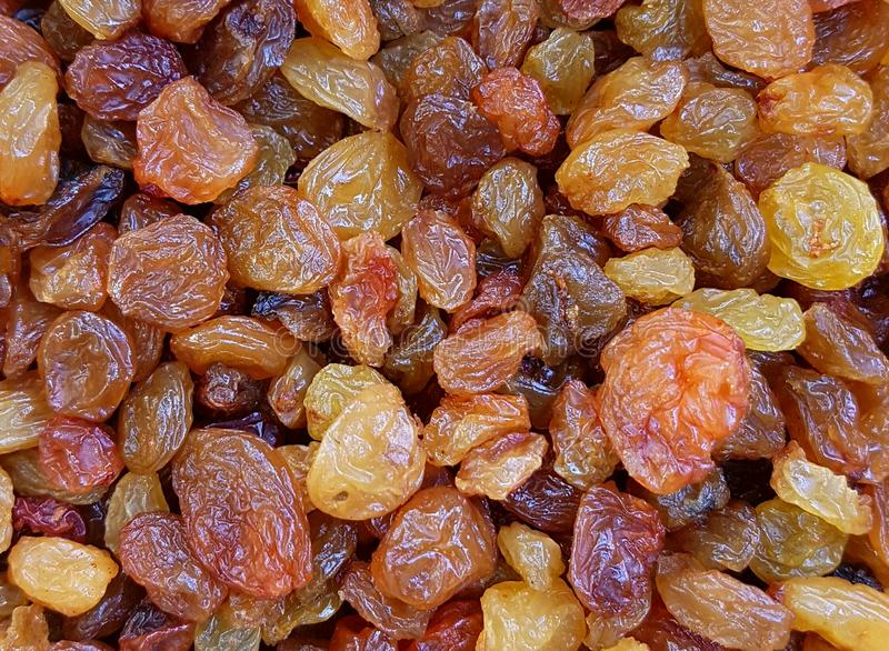 Brown and beige raisins. Abstract background of brown and beige or yellow raisins which are created by two varieties of dried grapes and used in the food stock images