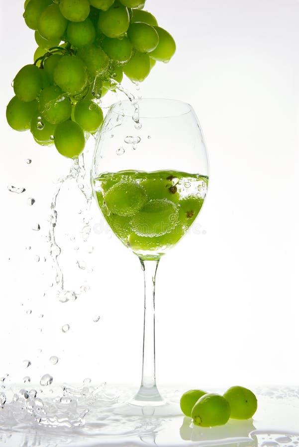 Raisin vert avec l'éclaboussure de l'eau dans le verre image libre de droits