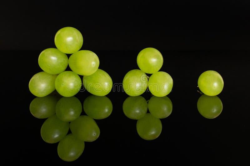 Raisin vert frais d'isolement sur le verre noir image stock