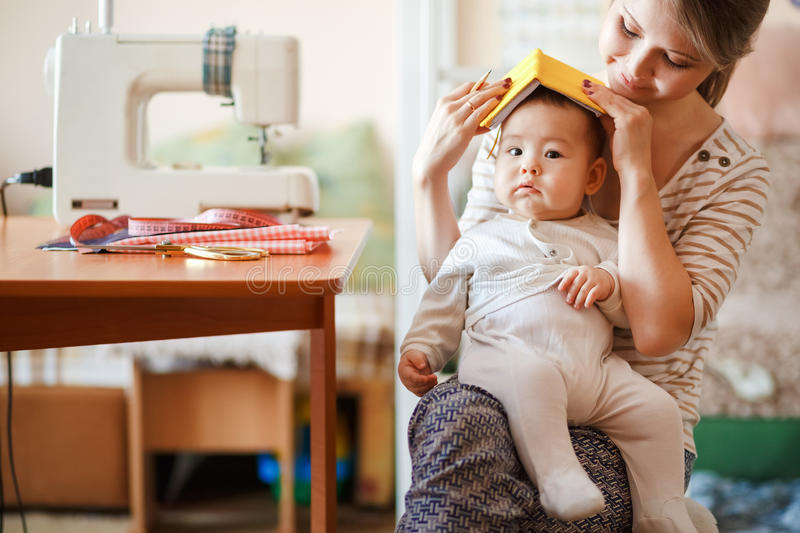 Raising children, child care, baby sitter. Mother and infant at home playing role-playing games. Cute fun parenting. stock images