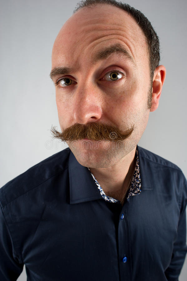 Raising an eyebrow. Portrait of a man with a moustache raising his left eyebrow in an unsure querying manner royalty free stock photo