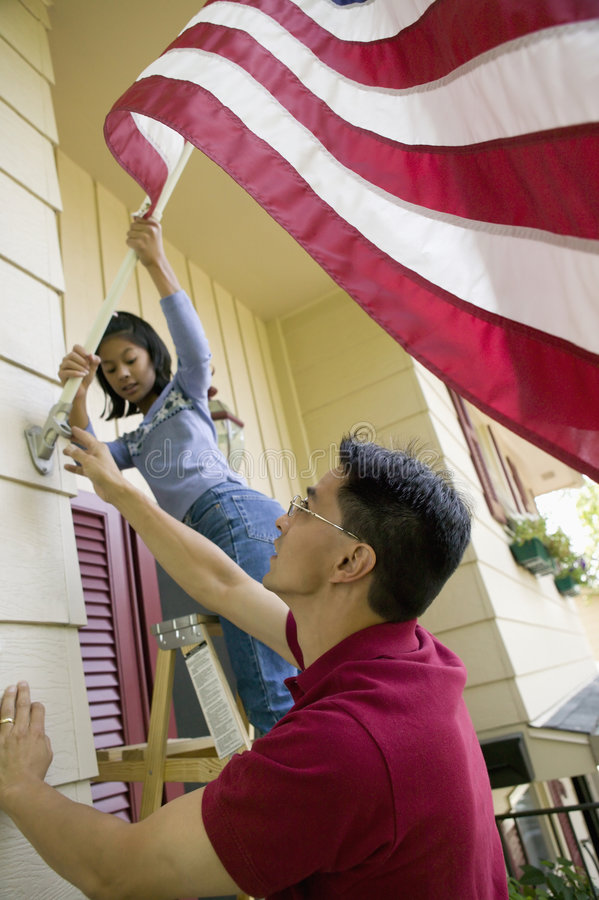 Raising the flag at home. Father and daughter put a US flag on their house royalty free stock photos