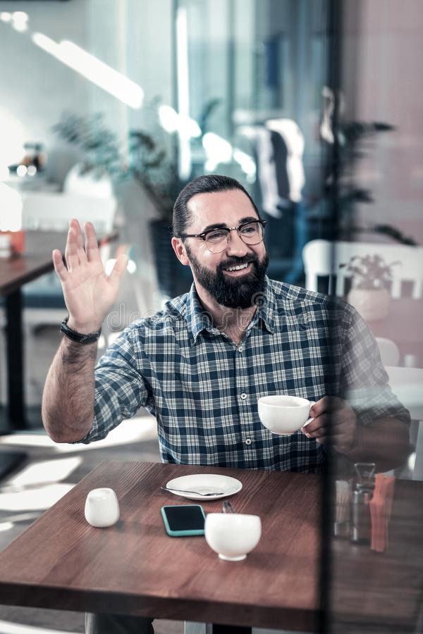 Bearded beaming man raising his hand meeting colleague in cafeteria royalty free stock image