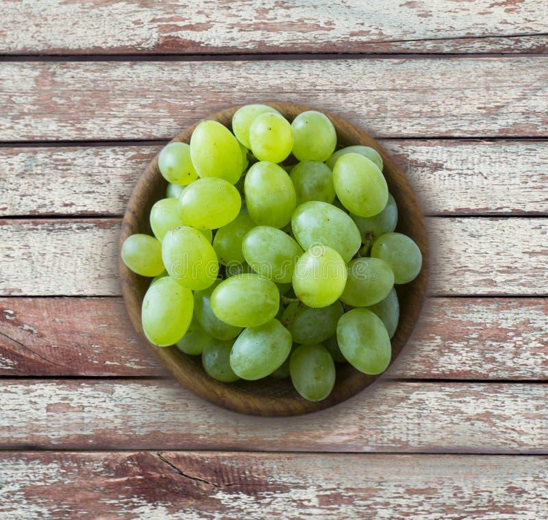 Raisins dans une cuvette en bois d'isolement sur la table en bois Raisins verts Kish Mish avec l'espace de copie pour le texte Ra photos stock