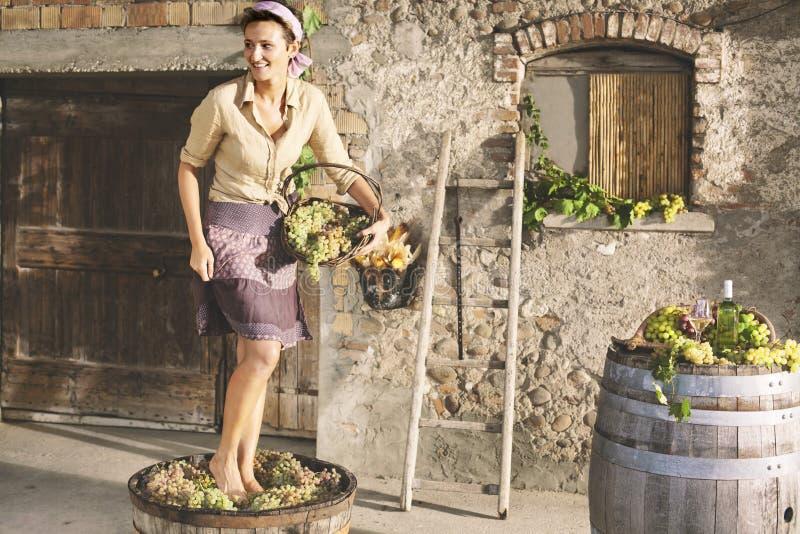 Raisins de broyage de femme dans un farnerhouse images stock