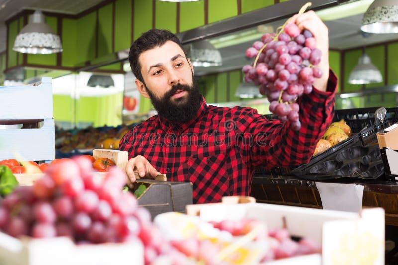 Raisins de offre d'heureux vendeur masculin dans la boutique photographie stock