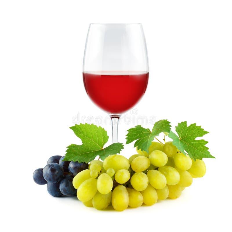 Raisins de table avec les feuilles fraîches vertes et le vin rouge en verre d'isolement images libres de droits