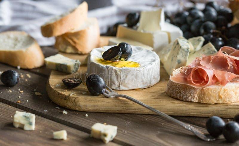 raisins et baguette de panneau de fromage Assortiment de fromage avec des baies sur le fond en bois images libres de droits