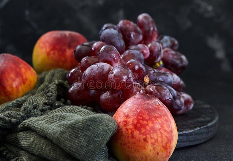 Raisins et p?ches sur un fond fonc? photos libres de droits