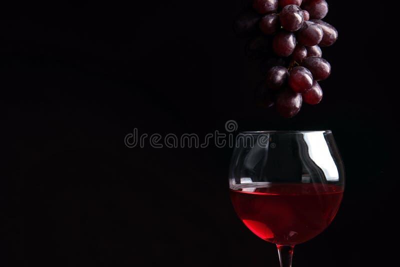 Raisins juteux mûrs frais au-dessus de verre avec le vin rouge images stock
