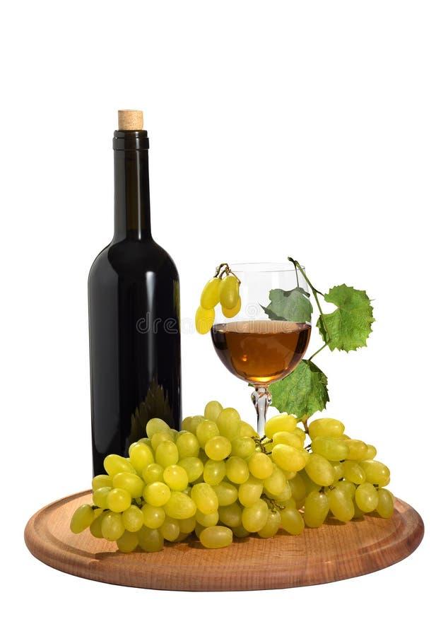 Raisins mûrs avec un verre de jus de raisins et d'une bouteille sur le fond d'isolement photographie stock
