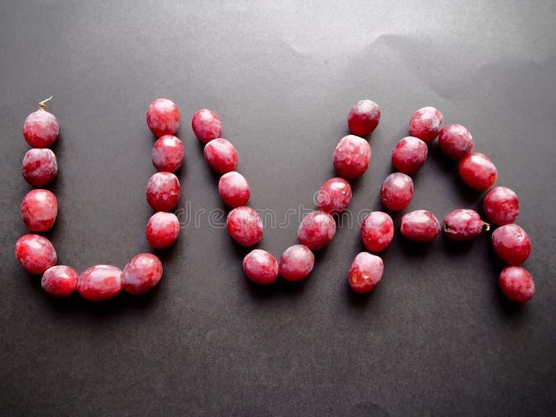 Raisins rouges écrivant le raisin dans l'Espagnol image libre de droits