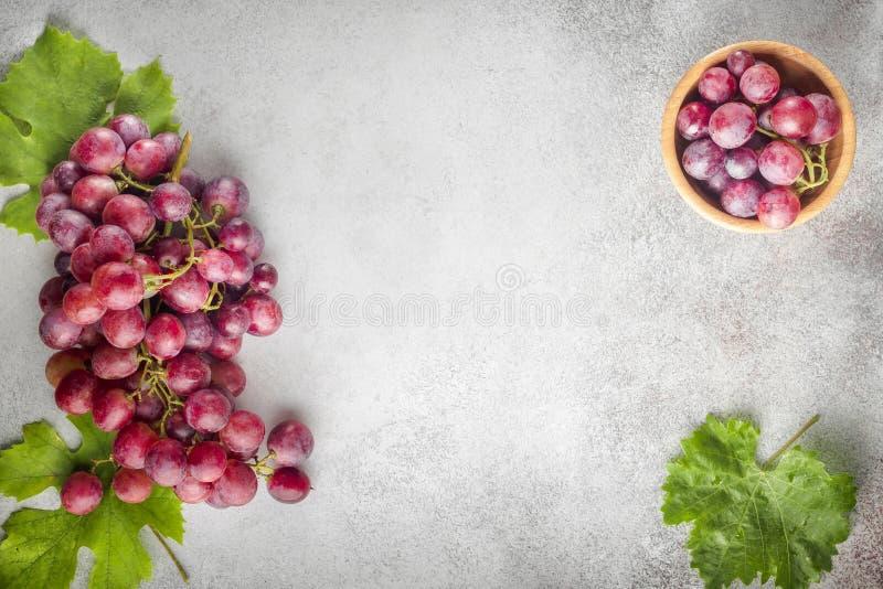 Raisins rouges avec des feuilles des raisins sur une table en pierre Vue supérieure Fre photo libre de droits