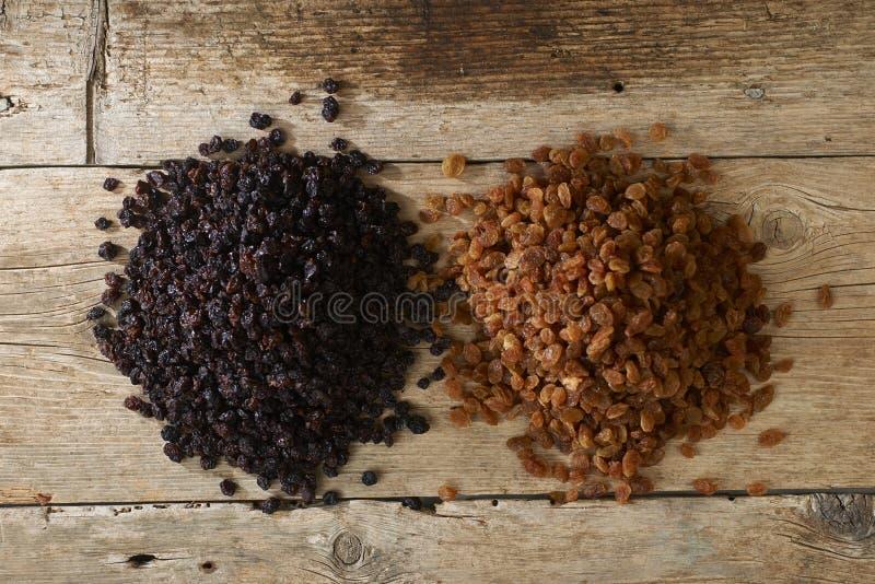 Raisins secs d'or et noirs au-dessus de table en bois images stock