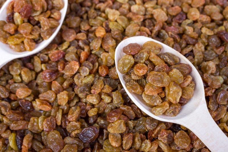 Raisins secs dans une cuillère en bois, plan rapproché, fond de nourriture photographie stock libre de droits