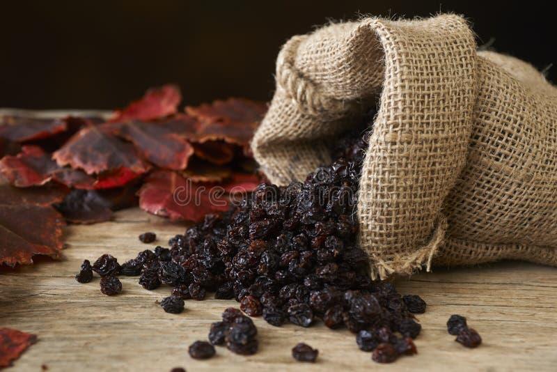 Raisins secs noirs dans le sac de toile de jute au-dessus de la table en bois photo libre de droits